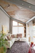 Comfortable leather sofa set with scatter cushions in bright living area wit sloping ceiling and steel girders