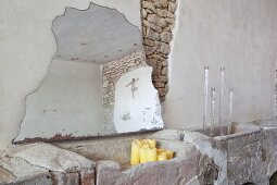 Fragment of mirror leaning against wall, candlesticks and candles in rustic interior