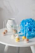 Colourful cake pops and blue pompom on table