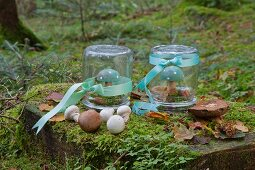 Painted wooden toadstools under upturned mason jars decorated with ribbons in woods