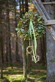 Kranz aus Eichenlaub mit Stoffbändern hängt im Wald