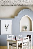 Set table in front of wall with 3D mouldings and niche