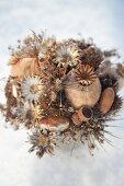 Gesteck aus Trockenblumen, Mohnkapseln und Eicheln