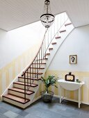 Steep staircase and dado painted in yellow stripes in foyer