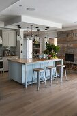 Dove-grey island counter and bar stools next to chimney breast with rustic, reclaimed-wood cladding in kitchen