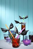 Various glasses with drinking straws decorated for Halloween party