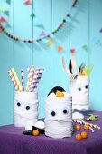 Hand-crafted mummy tins decorating table for Halloween