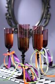 Dark Champagne flutes decorated with ribbons for Halloween