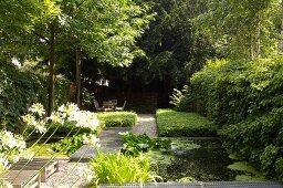 Garten mit Teich und Gittersteg, im Hintergrund schattiger Sitzplatz