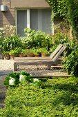 Holzliegen auf Kiesfläche im Garten und Pflanzen in Tontöpfen vor Fenster