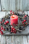 Red pillar candle in wreath of sloe branches and rose hips