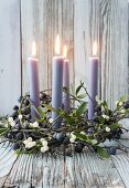 Four candles in wreath of sloe branches and mistletoe