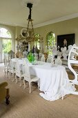 Long oval dining table and Baroque chairs in grand dining room