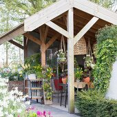 Various potted plants and hanging baskets in summer house with three open sides