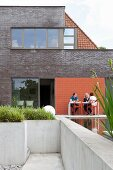 Modern brick extension with people sitting on concrete terrace and pool