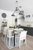 Dining table on grey and white striped rug in grey and white kitchen