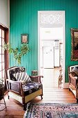 Old armchair in front of turquoise painted wall with passage