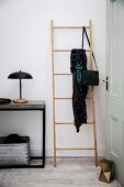 Bamboo ladder leans in the hallway next to a light console table