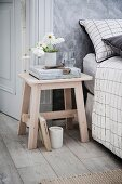 Wooden stool as a bedside table in the bedroom in shades of gray