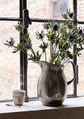 Blaue Disteln in einer Zinkkanne als Vase vor einem Fabrikfenster