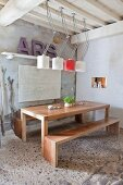 Simple, exotic-wood table and benches below designer lamps