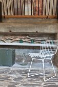 Stone floor, driftwood and white wire chair in rustic ambiance