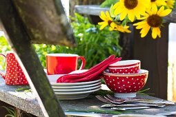 Red and white picnic crockery and cutlery on rustic wooden bench next to sunflowers