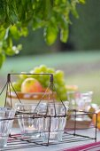 Tealight holders in vintage bottle carrier on picnic table