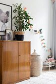 Retro sideboard, house plant and dolls' bed in corner of nursery