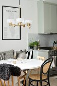 Round white table, bentwood chairs and retro lamp next to kitchen counter