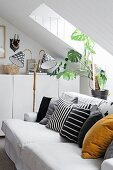 Various scatter cushions on comfortable sofa, retro standard lamp and house plant under sloping attic ceiling