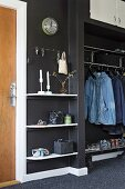 Fitted shelves and clothes rails on black wall