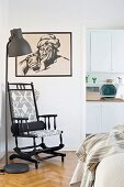 Black wooden rocking chair next to standard lamp and below black-framed drawing on wall