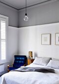 Bedroom corner with blue retro armchair and white-gray wall