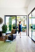 Elegant living area with black leather armchair and patio glazing, woman in front of sliding patio door