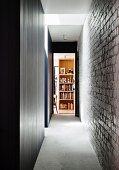 Narrow hallway with brick wall and gray carpeting