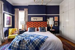 Double bed in the bedroom with dark blue wall and white built-in closet