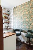 Dark green retro bar stools against floral wallpaper in kitchen