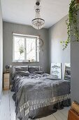 White board floor, chandelier and dreamcatcher in bedroom in shades of grey