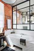 Glass and steel partition above bathtub in bathroom