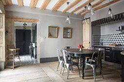 Ovaler Tisch mit Klassikerstühlen im Essbereich vor eingebauter Küchenzeile in Wandnische