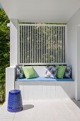 Built-in bench with cushion and decorative pillows on white veranda