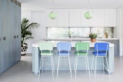 Simple kitchen in white-gray-blue with blue and green bar stools on a kitchen island