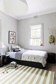 Grün-weiß gestreifter Teppich im schlichten Kinderzimmer