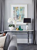 White orchid, vases and Fornasetti table lamp on console table in front of modern picture on gray wall