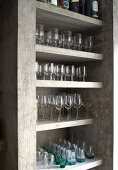 Neatly arranged glasses on concrete shelves