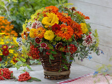 Late summer bouquet in homemade basket with wooden floor