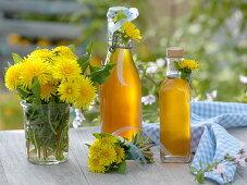 Dandelion syrup in bottles, small Taraxacum bouquet