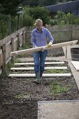 Woman placing wooden grates as paths at regular intervals in the beds