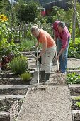 Man putting gravel on the path with shovel, woman pulling it straight with rake